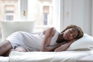 Woman in white dress sleeping on bed not morning person