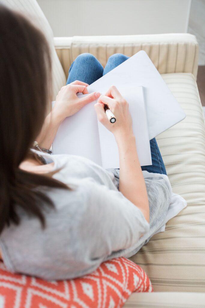 Woman journaling on sofa
