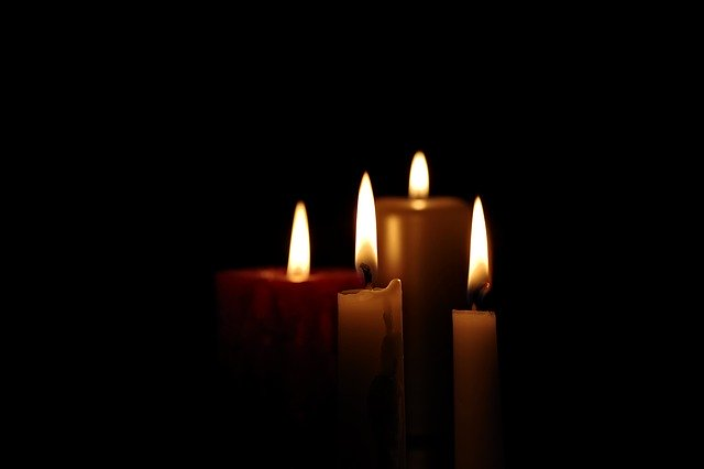 set of four candles in darkness