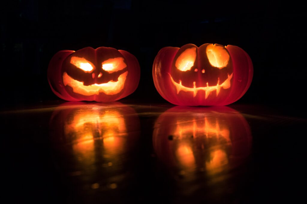 two jack-o'-lanterns carved with faces