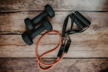 pair of dumbbells and workout band on wooden background